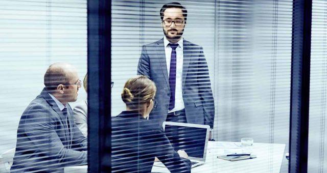 3 Personen stehen in einem Meetingraum
